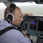 Russia's Prime Minister Vladimir Putin, wearing headphones, sits in the cockpit of a firefighting plane in Ryazan region